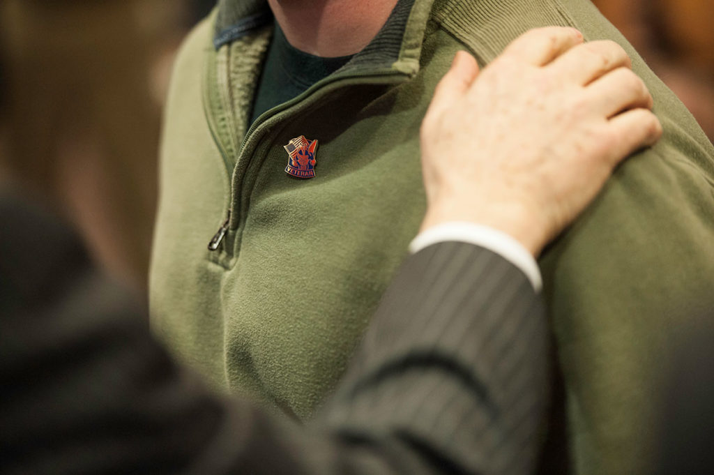 A close up of a University veterans pin on a person's shirt.