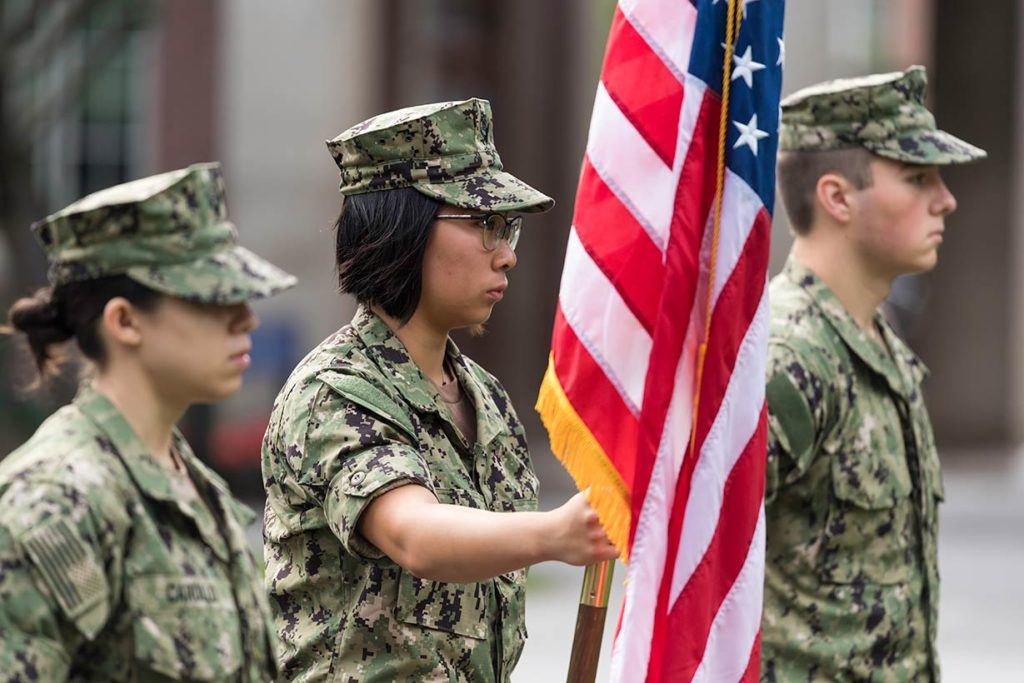 Service personnel standing vigil with an American flag.