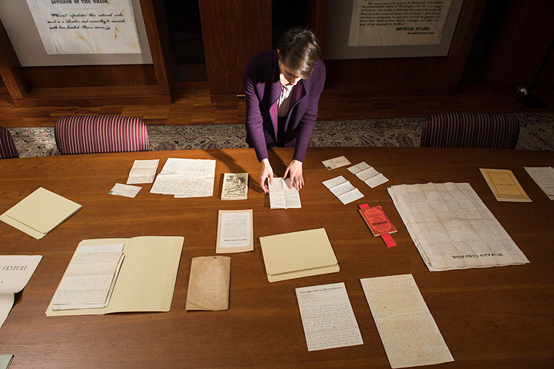 A person standing at a table of documents.