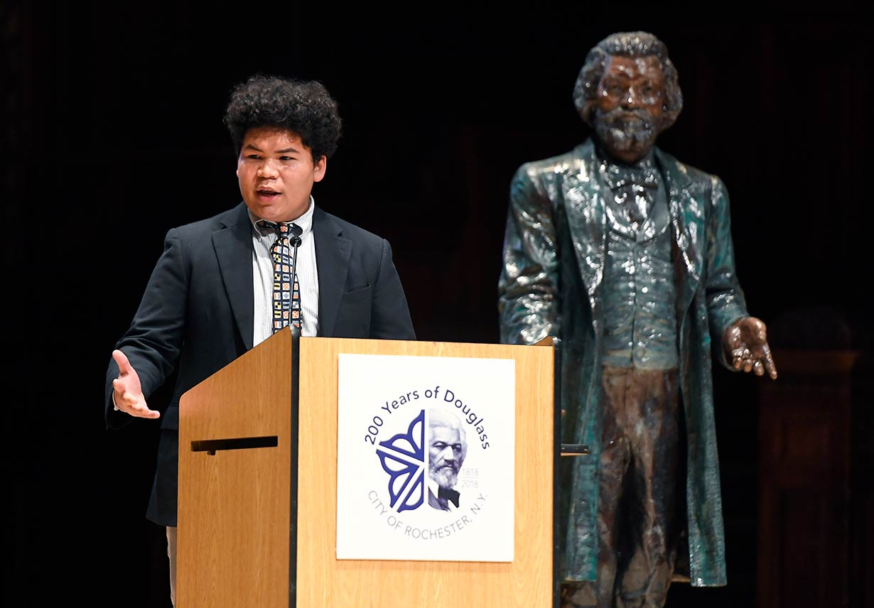 A person speaking from a podium with a statue of Frederick Douglass in the background.