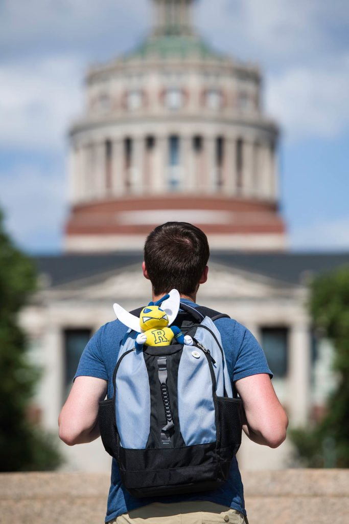 A student with a backpack looking towards Rush Rhees Library.