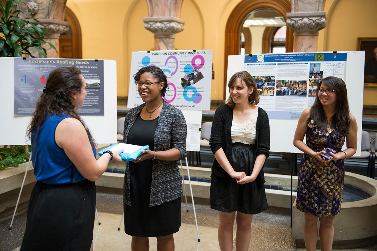 Three students at a poster session presenting their work.