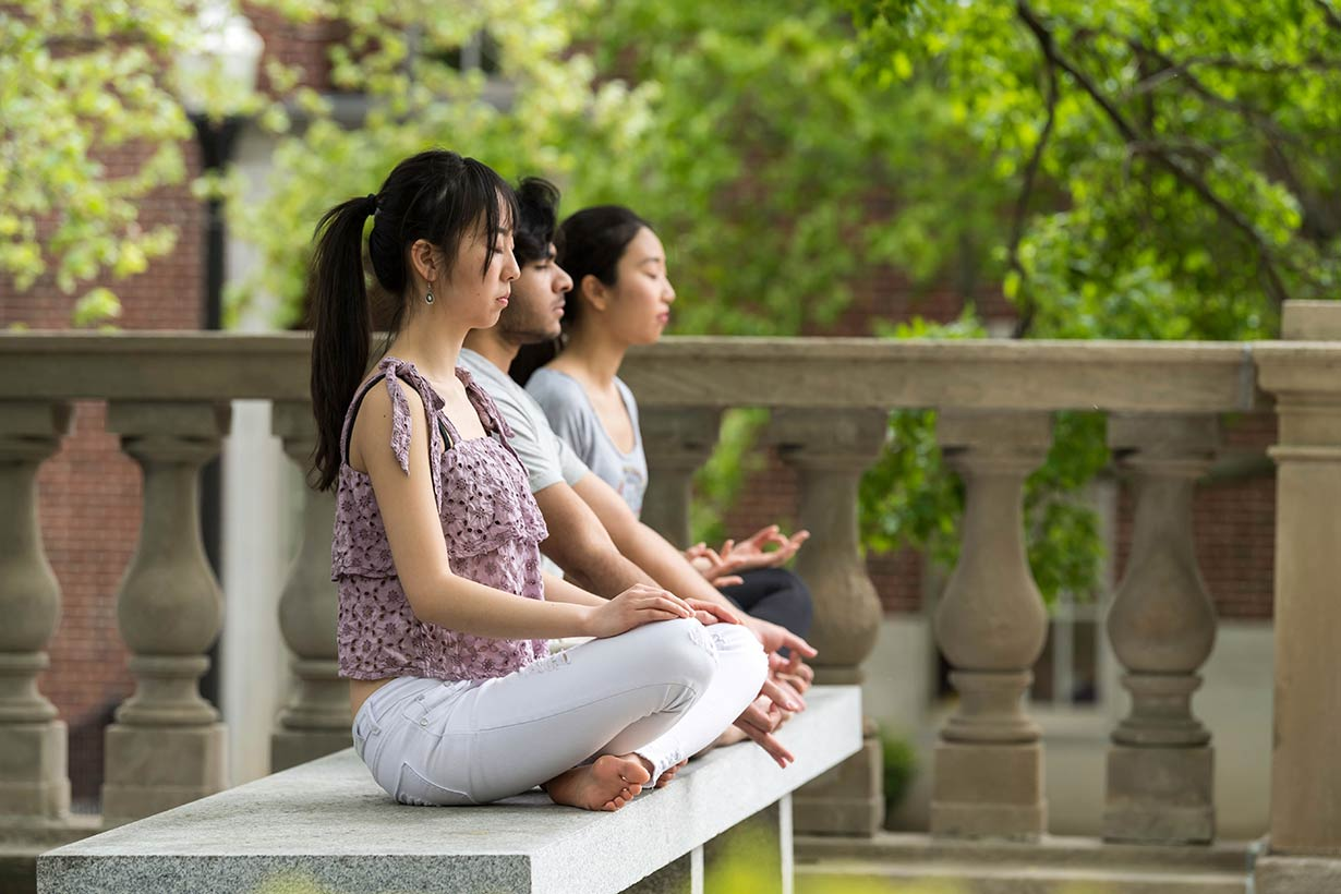 Three students sitting cross legged and practicing mindfullness on a bench in the quad.