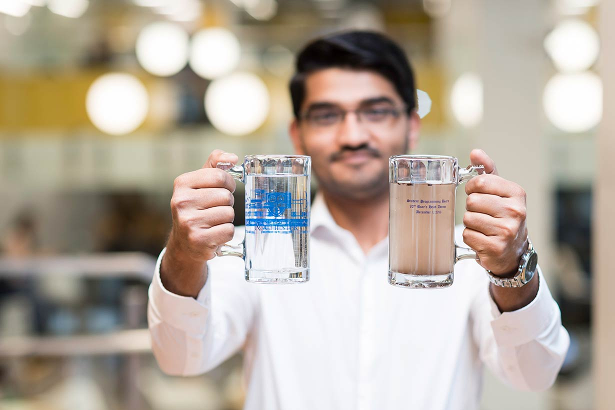 A Grand Challenges Scholar student holding tow glasses of water—one clean, and one dirty.