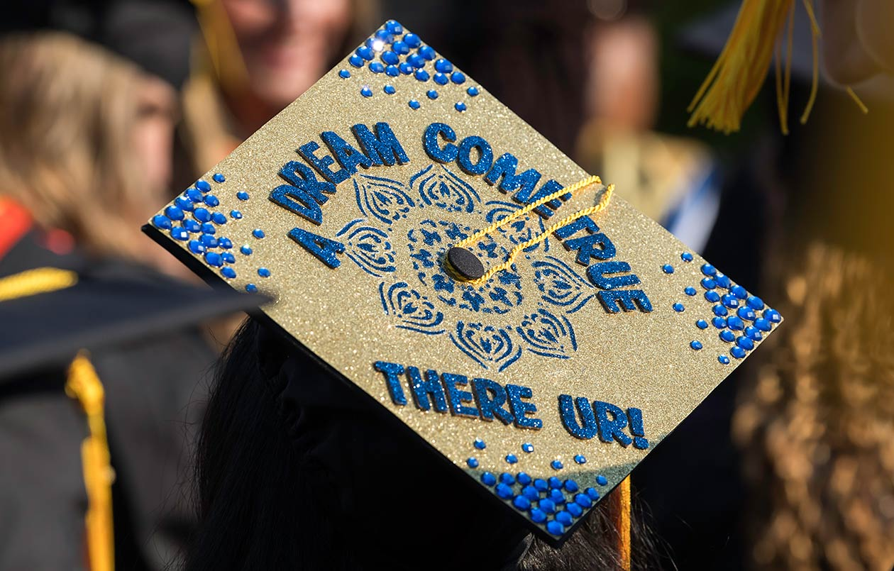 """The top of a decorated graduation cap that says """"A Dream Come True—There UR""""."""